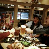 Professional wrestler Kris Wolf (center) raises a toast with fans Eiichi Nakazato (right) and Eishi Matsumoto at a Tokyo restaurant on March 12. | REUTERS
