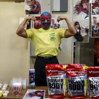 A man strikes a pose as he sells high protein foods outside a Stardom wrestling show in Tokyo on Dec. 23, 2015. | REUTERS
