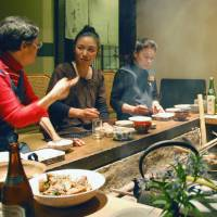 The authentic experience: Guests and hosts share a meal around the hearth at a minshuku in Ayabe, Kyoto Prefecture. Running a minshuku or ryokan — both of which involve looking after guests in the owner's home — is a lot more work than operating a standard guesthouse, where travelers generally take care of themselves. | KYODO