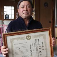 Susumu Tamura, a former base worker, holds a commendation for 40 years of work on U.S. installations. | JON MITCHELL