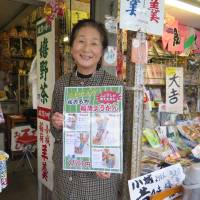 Service with a smile: Yoko Ueda holds a board explaining how to eat red bean paste sweets at her shop in the city of Kashiwa, Saga Prefecture, on Feb. 21. | KYODO