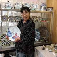 Potter Yoshie Urakawa holds an Arita porcelain plate at her shop in the town of Arita, Saga Prefecture, on Feb. 22. | KYODO