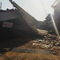 Only a few blocks from Mashiki Town Hall, this unidentified building spilled its roof tiles into the street. The shops beside it also sustained substantial damage.   LIAM NOLAN