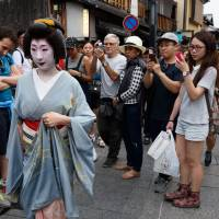 A capital day out: Foreign tourists corner a geisha (known in Kyoto as a geiko) in the historic Gion district. With the number of foreign tourists in Kyoto at record levels, there's just no room for Japanese sightseers anymore. | BLOOMBERG