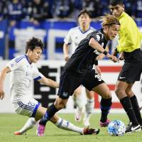 Gamba Osaka's Takashi Usami (right) controls the ball against the Suwon Samsung Bluewings in the Asian Champions League on Tuesday in Suita, Osaka Prefecture. The Bluewings defeated Gamba 2-1. | KYODO