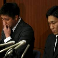 Sportsmen Kenichi Tago (left) and Kento Momota deliver an apology. Their hair, which was light brown on Thursday, was newly dyed black, an apparent gesture of remorse. | REUTERS
