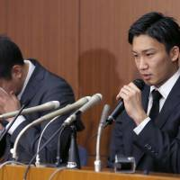Kento Momota speaks as Kenichi Tago cries into a handkerchief during a news conference on Friday. | AP