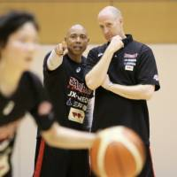 Corey Gaines (left) speaks to Japan national women's basketball team assistant coach Tom Hovasse during practice at the National Training Center on Monday. | KAZ NAGATSUKA
