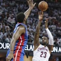 Cleveland's LeBron James (right) shoots over Detroit's Andre Drummond during the Cavaliers' 106-101 win on Sunday. | AP