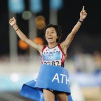 Mizuki Noguchi crosses the finish line to win gold in the women's marathon at the 2004 Athens Olympics. Noguchi was also the 2003 silver medalist at the world championships. | KYODO