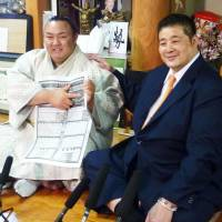 Newly promoted sekiwake Kotoyuki (left) points to his name on the new ranking for the Summer Grand Sumo Tournament with his stable master, Sadogatake, sitting at his side during a news conference in Matsudo, Chiba Prefecture, on Monday.   KYODO
