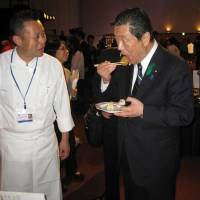 Agriculture Minister Hiroshi Moriyama samples gibier items at the 'Gibier Corner' of the G7 Agriculture Ministers' Meeting welcome reception, as chef Norihiko Fujiki looks on.   MINISTRY OF AGRICULTURE, FORESTRY AND FISHERIES