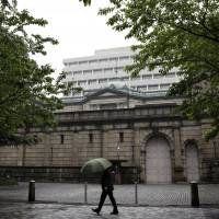 A pedestrian passes the Bank of Japan headquarters in Tokyo on a rainy day in April. | BLOOMBERG