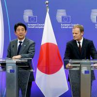 Prime Minister Shinzo Abe (left), European Council President Donald Tusk (center) and European Commission President Jean-Claude Juncker talk to the media before a working dinner at the EU Council in Brussels on Tuesday. | REUTERS