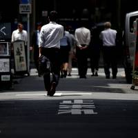 Pedestrians walk through a Tokyo business district on Tuesday. Japan's job availability rose to the highest level in over 24 years. | REUTERS