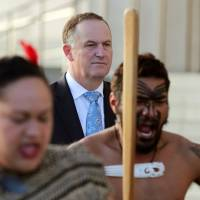 New Zealand Prime Minster John Key looks on as Maori performers greet French Prime Minister Manuel Valls in Auckland on May 2. | AFP-JIJI