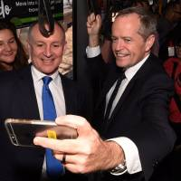 The premier of South Australia, Jay Weatherill (left), poses with Labor Party leader Bill Shorten on an Adelaide tram during a campaign event on Tuesday. | REUTERS