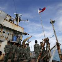 Philippine Marines stand on the Sierra Madre, a dilapidated Philippine Navy ship that was run aground in 1999 and became a Philippine military detachment on the disputed Second Thomas Shoal, part of the Spratly Islands in the South China Sea, in this March 2014 file photo. | REUTERS