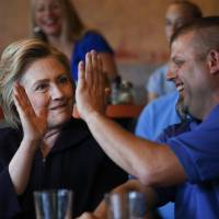 Democratic presidential candidate Hillary Clinton high fives Scott Conley while speaking to steelworkers in Ashland, Kentucky, Monday.   AP