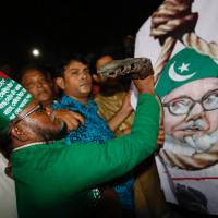 A Bangladeshi man throws a shoe at a Motiur Rahman Nizami poster to celebrate the execution of the Jamaat-e-Islami party's senior leader outside Dhaka's central jail early Wednesday. Nizami is the fifth man to be hanged as three other senior colleagues from his Islamist party and another senior leader of main opposition Bangladesh Nationalist Party led by former Prime Minister Khaleda Zia have been hanged since 2013. | AP