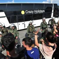Migrants and refugees leave by bus as solidarity groups protest behind a line of riot police during the forced evacuation of a makeshift camp close to the Greece-Macedonia border near the village of Idomeni on Tuesday. Greek police on May 24 moved hundreds of migrants out of the overcrowded camp of Idomeni, launching a major operation to clear up the squalid tent city where thousands fleeing war and poverty had lived for months. | AFP-JIJI