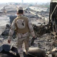 Fighters from the Iraqi pro-government forces inspect the damage at the Albu Aitha bridge north of Ramadi following an attack a military source said was carried out by the Islamic State (IS) group on Thursday. | AFP-JIJI