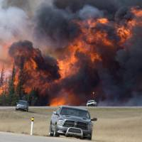 Canadian wildfire explodes in size, approaches oil sands project