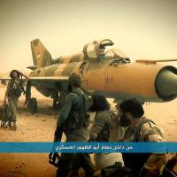 This image posted on the Twitter account of Syria's al-Qaida-linked Nusra Front last September shows fighters from the group gathering around a Syrian regime aircraft, inside the Abu Zuhour air base, in northern Syria's Idlib province.   AP