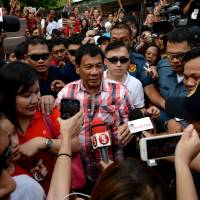 Rodrigo Duterte, who was set to become the next Philippine leader after garnering an insurmountable election lead, leaves after casting his vote at Daniel Aguinaldo National High School in the southern city of Davao on Monday. | AFP-JIJI