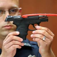 A police officer holds up the gun that George Zimmerman used to kill Trayvon Martin during Zimmerman's murder trial in Seminole circuit court in Sanford, Florida, in June 2013.   REUTERS