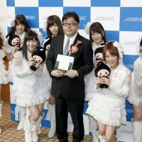 Yasushi Akimoto, producer of AKB48 and its sister idol groups, including HKT48 in Fukuoka, poses with AKB48 members in May 2013. | KYODO