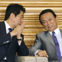Prime Minister Shinzo Abe talks with Finance Minister Taro Aso before a Cabinet meeting Tuesday. | KYODO