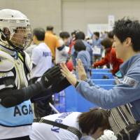 A Toyota Motor Corp. employee high fives a player during the Special Olympics on Feb. 13 in the city of Niigata. | KYODO
