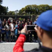 Chinese tourists pose for a photograph outside the Imperial Palace in Tokyo on April 15. | BLOOMBERG