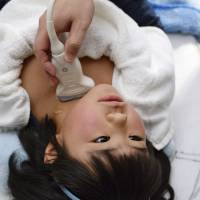 A girl is screened for thyroid cancer in February in the village of Hirata, Fukushima Prefecture. | KYODO