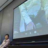 The father of a child diagnosed with thyroid cancer uses Skype to address a presentation in Tokyo on March 12. | KYODO