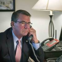 U.S. Secretary of Defense Ash Carter speaks on the telephone with Japanese Defense Minister Gen Nakatani in this photo released by the U.S. Department of Defense on Saturday. | REUTERS