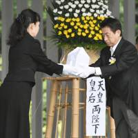 Welfare minister Yasuhisa Shiozaki transfers the remains of an unidentified soldier from World War II to an official at Chidorigafuchi National Cemetery in Tokyo on Monday. | KYODO