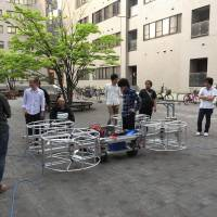 Engineers developing a flying car look at a full-size prototype in Tokushima Prefecture.   CHUNICHI SHIMBUN