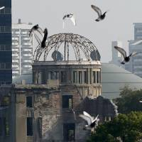 Doves fly over the atomic bomb dome in Hiroshima. A majority of people interviewed in the streets of Tokyo on Wednesday said U.S. President Barack Obama does not need to say sorry during his May 27 visit to Hiroshima. | REUTERS