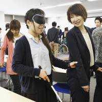 Corporate employees take training in Tokyo's Shinagawa Ward on May 10 that helps them understand how to interact with people with disabilities and the elderly. | KYODO