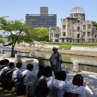 A volunteer at Peace Memorial Park in Hiroshima explains the devastation caused by the U.S. atomic bombing of the city to visiting students on May 17. | SATOKO KAWASAKI