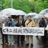 Plaintiffs head for the Kochi District Court on Monday to sue the government for redress linked to their irradiation by U.S. hydrogen bomb tests in the Pacific Ocean in 1954. | KYODO