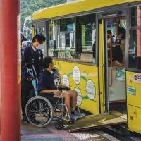 A man in a wheelchair rides a loop bus in Nara Prefecture. A new law requires government agencies and private businesses to remove 'social barriers' for people with impairments, including ensuring their access to public transportation. | ISTOCK