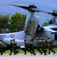 Self-Defense Forces personnel move to unload aid supplies from a U.S. military Osprey at Hakusui Sports Park in Minamiaso, Kumamoto Prefecture, on April 18. | REUTERS