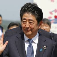 Prime Minister Shinzo Abe waves after a news conference at the Group of Seven summit in Shima, Mie Prefecture, on Friday. | AP
