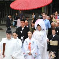 Jonathan Madrid, 24, and Nao Sasaki, 30, are led by priests to the wedding hall at Tokyo's Meiji Jingu on Saturday. | YOSHIAKI MIURA