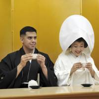 Jonathan Madrid and Nao Sasaki rehearse drinking nuptial cherry blossom tea together before their wedding ceremony at Meiji Jingu Shrine in Tokyo on Saturday. | YOSHIAKI MIURA