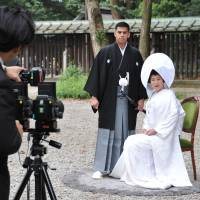 Jonathan Madrid and Nao Sasaki have their picture taken after their wedding ceremony at Meiji Jingu in Tokyo on Saturday. | YOSHIAKI MIURA