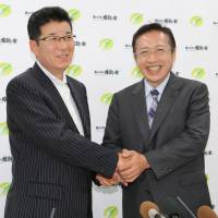 Yoshimi Watanabe (right), who is running for the Upper House on the Osaka Ishin no Kai ticket, meets with Osaka Ishin leader Ichiro Matsui at a news conference to announce his candidacy on May 16 in the city of Osaka. | KYODO